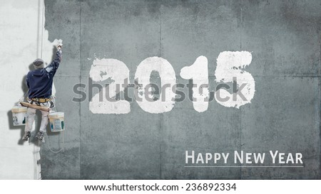 Building painter hanging from harness painting a wall with the words Happy New Year 2015 - stock photo