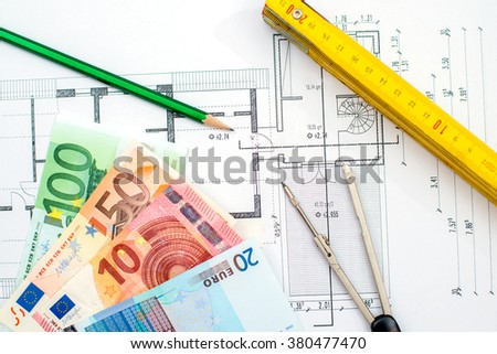 building plan with money pencil folding yardstick and compass - stock photo