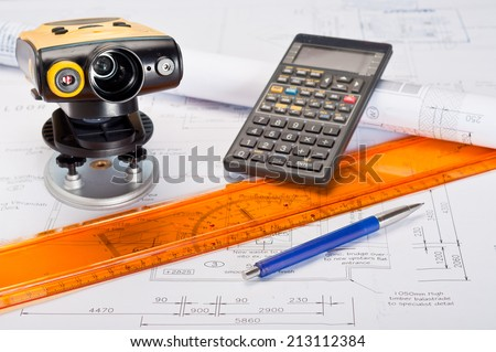 Building plans with laser distance measurement device and calculator - stock photo