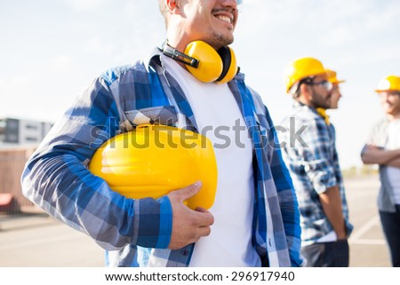 building, protective gear and people concept - close up of builder holding yellow hardhat or helmet at construction site - stock photo