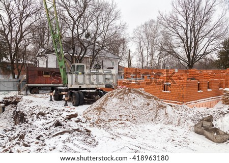 building site coated with snow stoped costruction of house - stock photo