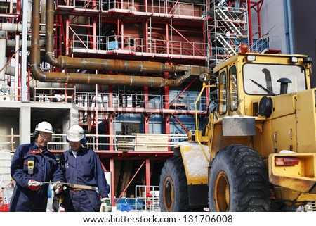 building site engineers with factory constructions in the background - stock photo