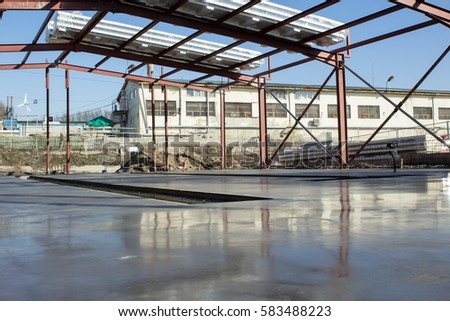 Building site - freshly polished cement slab with reflections and metal construction
