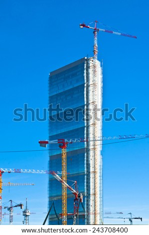 building site with cranes with skyscraper under construction in the blue sky background - stock photo