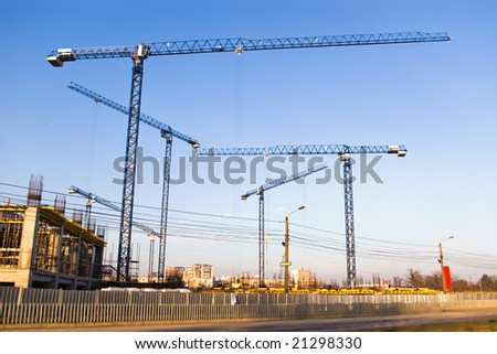 building site with six cranes on clear blue sky