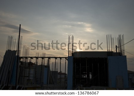 Building site with unfinished house frame during sunset