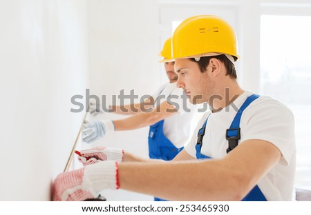 building, teamwork, measurement and people concept - group of builders s in hardhats with measuring tape working indoors - stock photo