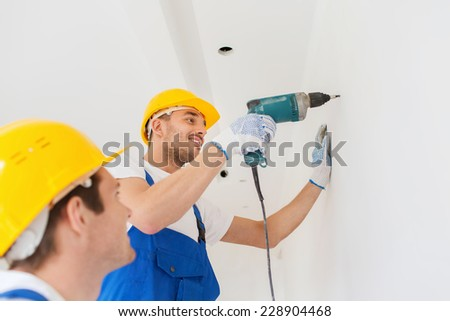 building, teamwork, working equipment and people concept - group of smiling builders s in hardhats with electric drill indoors - stock photo