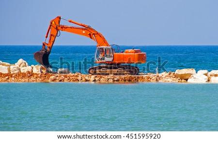 building the jetty with heavy excavator machine - stock photo