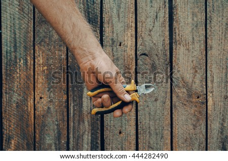 Building tools composition, hand  with tools, wooden desk - stock photo