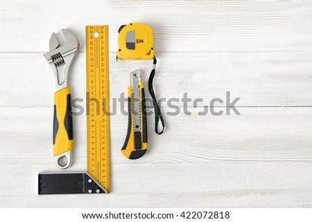 Building tools including centimeter ruler, wrench and cutter placed in the right side on wooden surface with open space. Top view composition. Measurement. Fixing and cropping. Hand tool. Tools for - stock photo