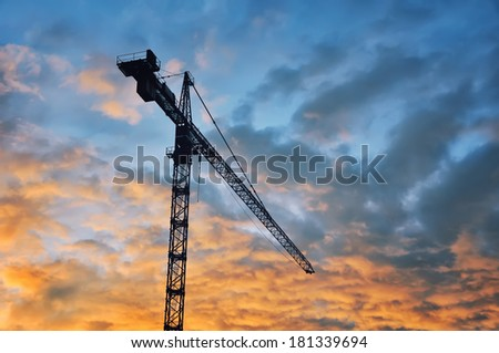 Building tower crane with sunset sky at the background - stock photo
