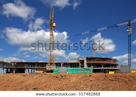 building under construction and cranes under a blue sky