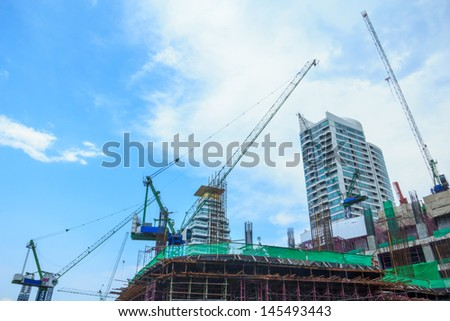 Building under construction and working cranes with blue sky