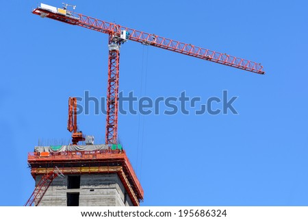 Building under construction site with red crane ,	engineer works site ,blue sky background - stock photo