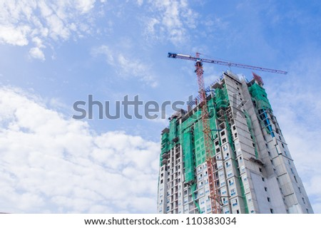 Building under construction with crane operating and blue shy background - stock photo
