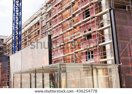 building under construction with scaffolding and crane - stock photo