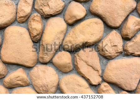 Building wall texture made of big rough yellow stones pressed into cement