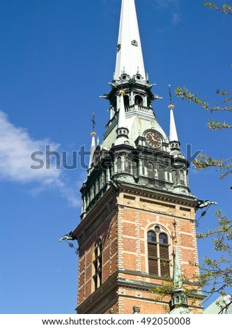 building with a tower in the center of the city on a background of blue sky