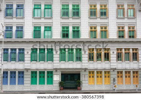 building with colorful windows. Window frame. Building with colorful frames. A lot of colorful windows. Colorful windows. Green window, yellow window, blue window. Sunny windows. Windows texture. - stock photo