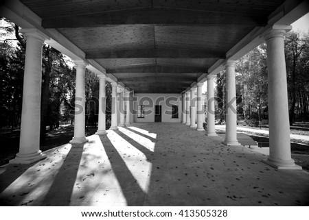 building with columns in the park, black and white photo - stock photo