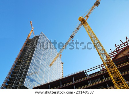 Building with cranes on sky background