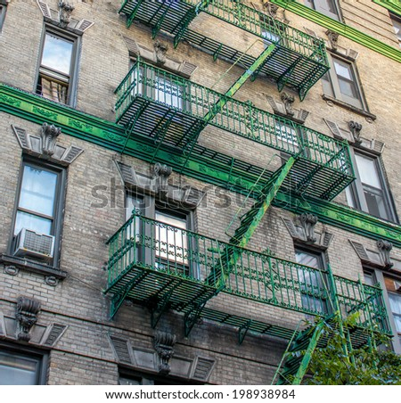 Building with green ladders for fire escape, Mott Street New York. - stock photo