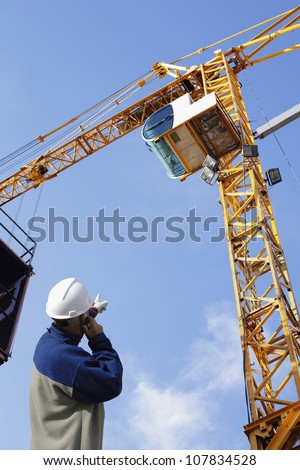 building worker directing large mobile crane inside construction site - stock photo