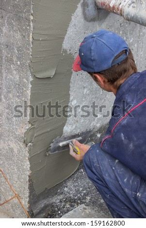 building worker spreading mortar on concrete wall with a trowel - stock photo