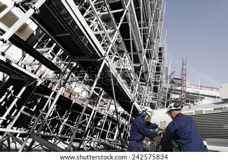 building workers with machinery inside large scaffolded site - stock photo