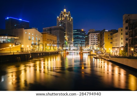 Buildings along the Milwaukee River at night, in Milwaukee, Wisconsin. - stock photo