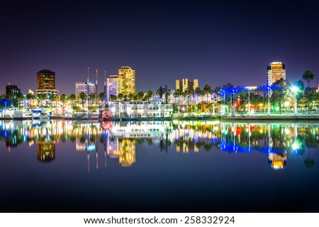 Buildings and boats reflecting in the harbor at night, seen from Shoreline Aquatic Park in Long Beach, California. - stock photo