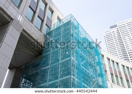 Buildings and scaffolding (curing net) - stock photo