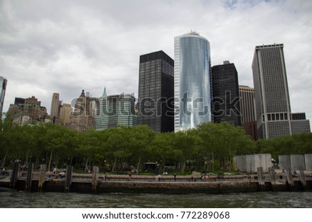 Buildings at lower Manhattan and Battery Park with dark cloudy sky