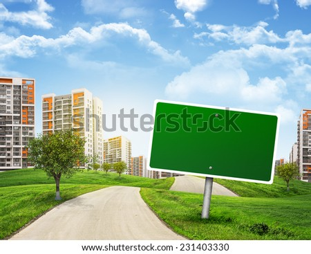 Buildings, green hills and road with empty road sign against sky with clouds. Business concept - stock photo