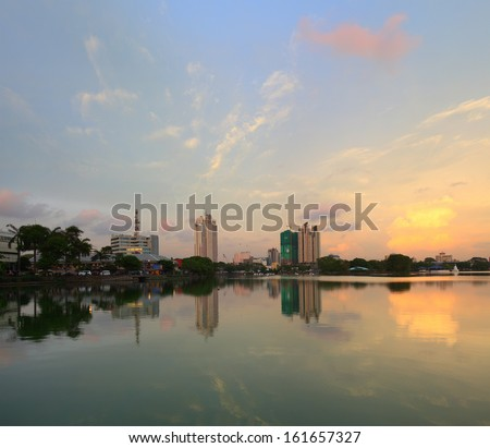 Buildings in a city of Colombo with reflection in a pond at sunset. Sri Lanka
