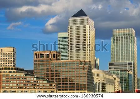 Buildings in Canary Wharf business district, London UK with blue sky and clouds - stock photo