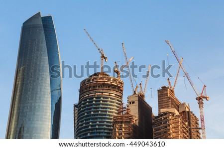 Buildings in construction with cranes on their top