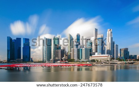 Buildings in Singapore skyline with beuatiful moving cloud - stock photo