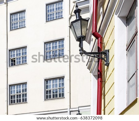 Buildings in the old town in Tallinn. Old forged lantern. The facade of the building with windows.