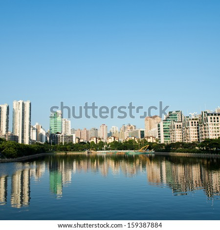 Buildings of a city with reflection in water. China