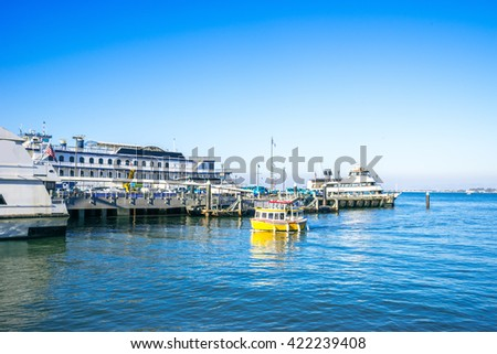 buildings on dock with yacht and sail boats on tranquil water - stock photo