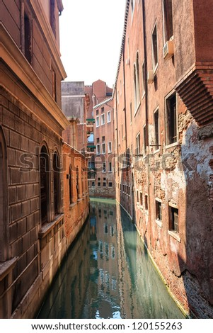 Buildings reflected in a small sub-canal in the city of Venice