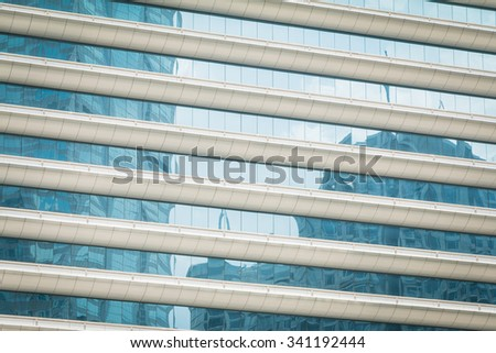 Buildings reflected in windows of modern office building - stock photo