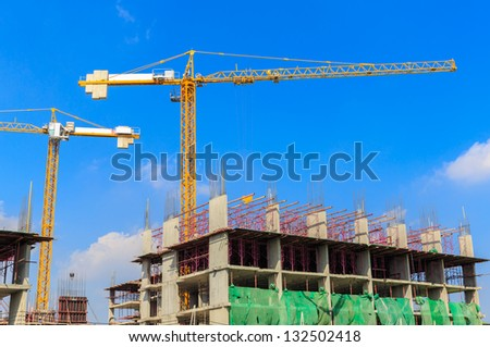 buildings under construction with cranes against white cloud and blue sky