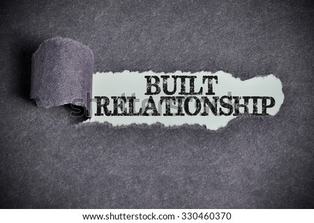 built relationship word under torn black sugar paper. - stock photo