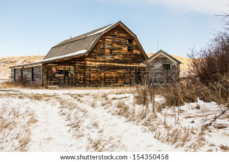 Built to look like a barn due to the agricultural area it is in, this community hall and outhouse are the last remaining structures in a small, rural Montana town - stock photo