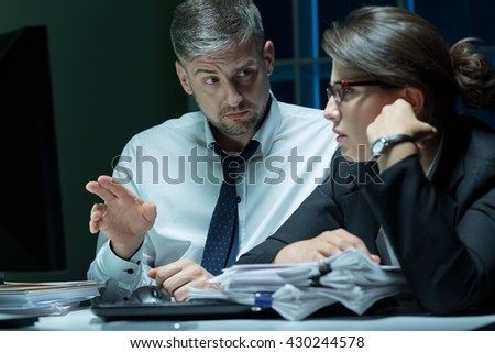 Buinesspeople working together at office at night, sitting beside desk - stock photo