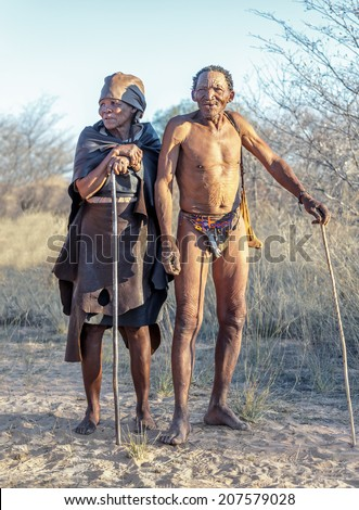 BUITEROS, NAMIBIA - JULY 17, 2014: Hunters Bushmen and their wives posing tourists. The San people, also known as Bushmen are members of various indigenous hunter-gatherer peoples of Southern Africa. - stock photo
