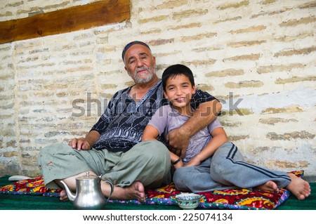 BUKHARA, UZBEKISTAN - JUNE 7, 2011: Unidentified Uzbek father and son sit on the carpet in Uzbekistan, Jun 7, 2011.  81% of people in Uzbekistan belong to Uzbek ethnic group - stock photo